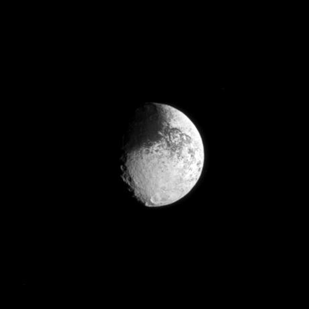 The two-toned surface of Saturn's moon Iapetus is demonstrated in the dark region of the moon visible on the top left and the bright crater in the lower right of this portrait captured by NASA's Cassini spacecraft.