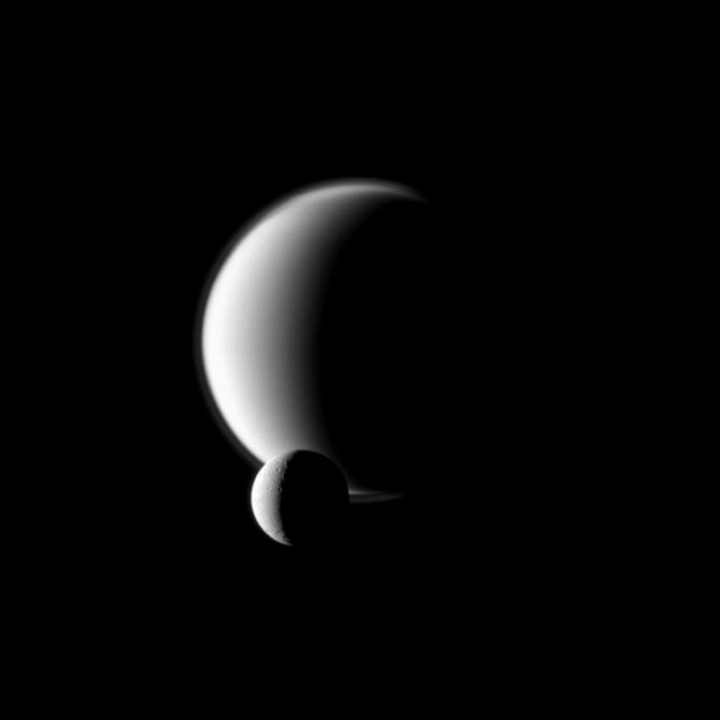 Saturn's moon Dione passes in front of the larger moon Titan, as seen from NASA's Cassini spacecraft. This image is part of a mutual event sequence in which one moon passes close to or in front of another.