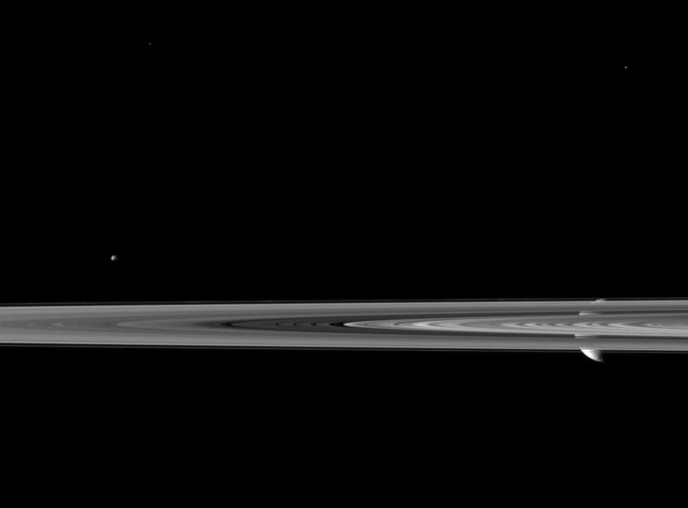 Saturn's second largest moon Rhea pops in and out of view behind the planet's rings in this image from the Cassini spacecraft, which includes the smaller moon Epimetheus.