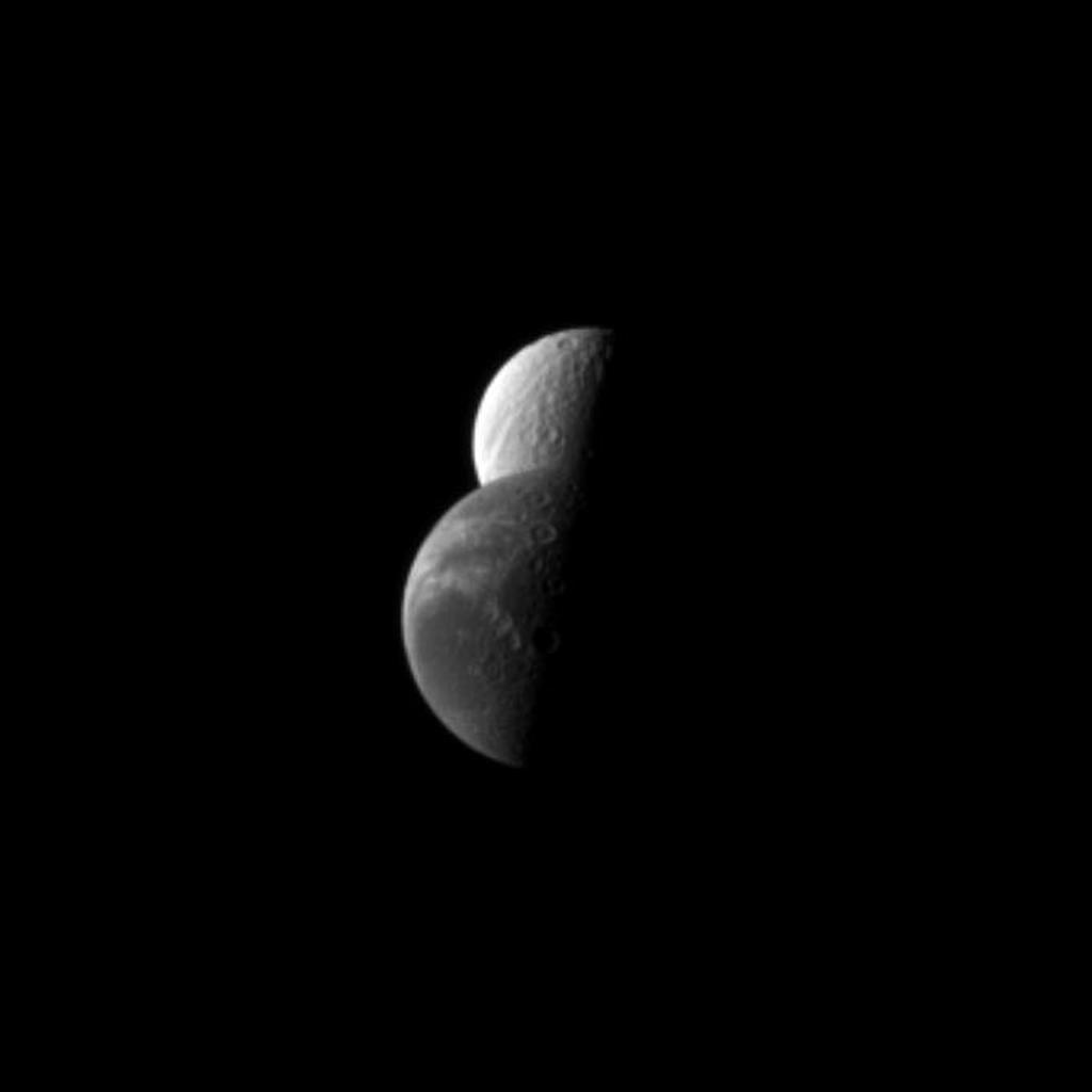 Saturn's moon Dione passes by the moon Tethys in this NASA Cassini spacecraft depiction of a 'mutual event' in which one moon passes close to or in front of another moon.