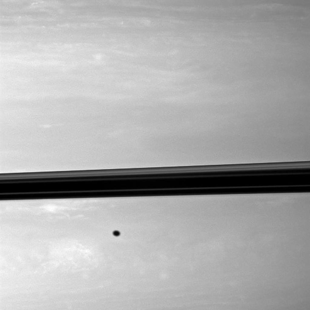 Appearing like a freckle on the face of Saturn, a shadow from the moon Enceladus blemishes the planet just below the ringplane in this NASA Cassini spacecraft image.