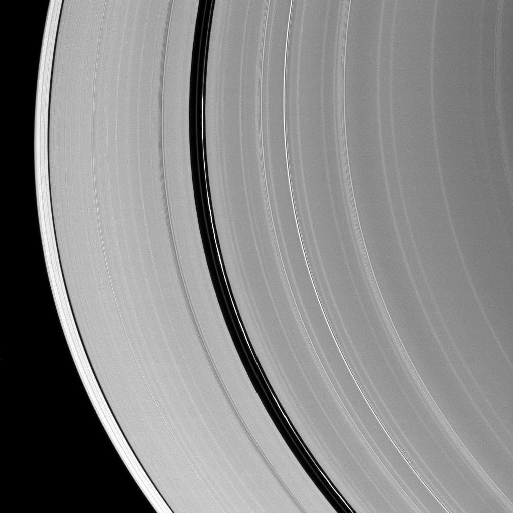 Kinky, discontinuous ringlets occupy the Encke Gap in Saturn's A ring in the middle of this NASA Cassini spacecraft image; parts of these thin ringlets cast shadows onto the A ring.