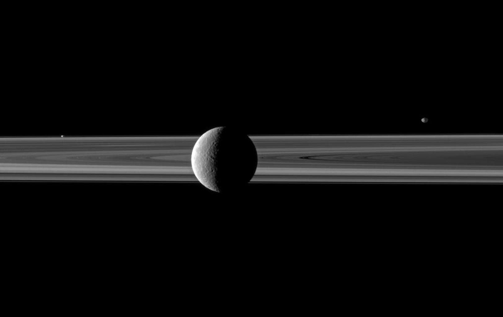 A pair of small moons join Saturn's second largest moon in this NASA Cassini spacecraft image spotlighting Rhea in front of the rings. Janus is seen beyond the rings on the right and Prometheus is visible between the main rings and thin F ring on left.