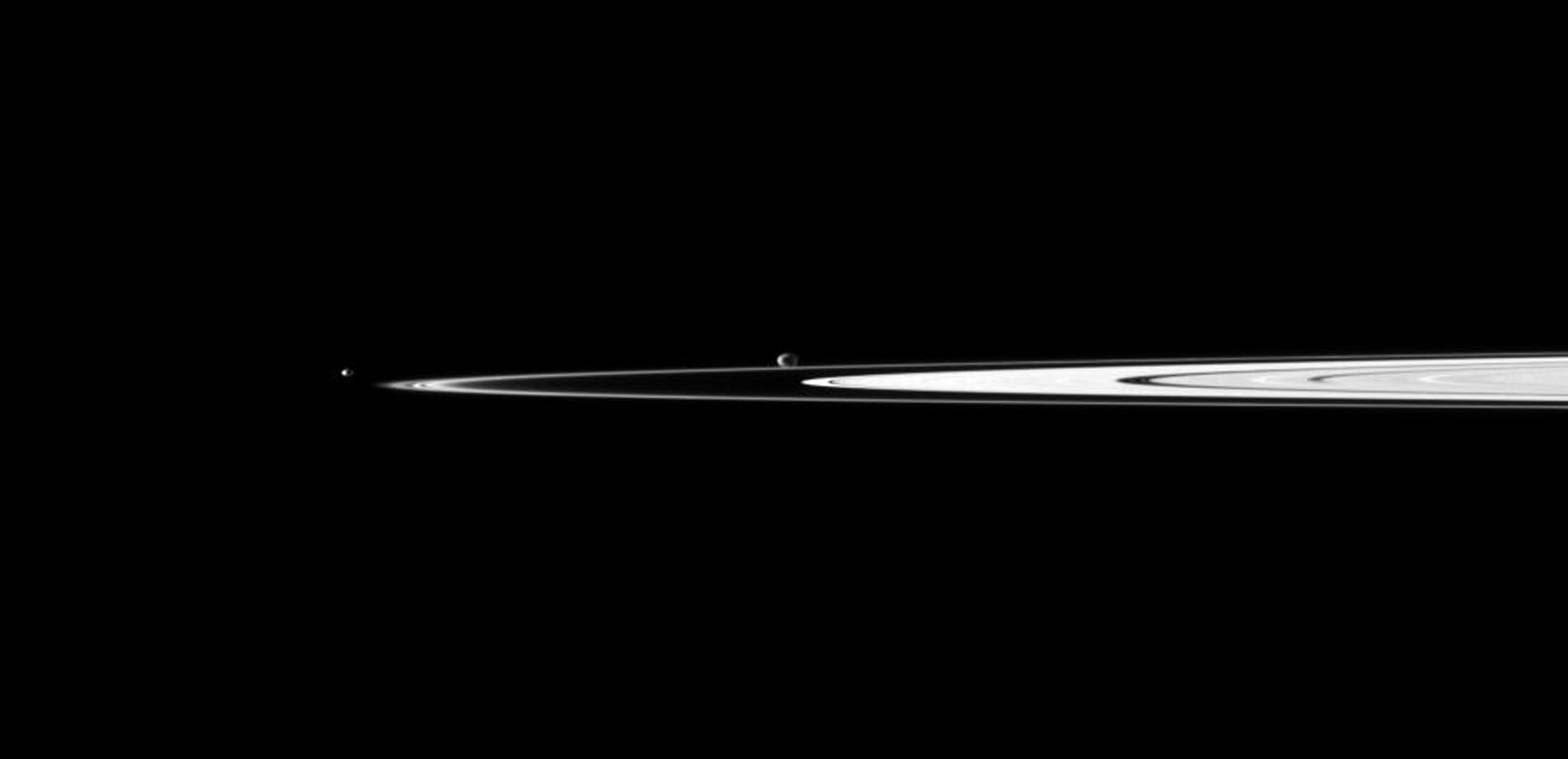 A pair of Saturn's small moons orbit near the planet's rings, which appear well illuminated in this view captured by NASA's Cassini spacecraft. Janus is near the center of the image and Pandora is on the left.