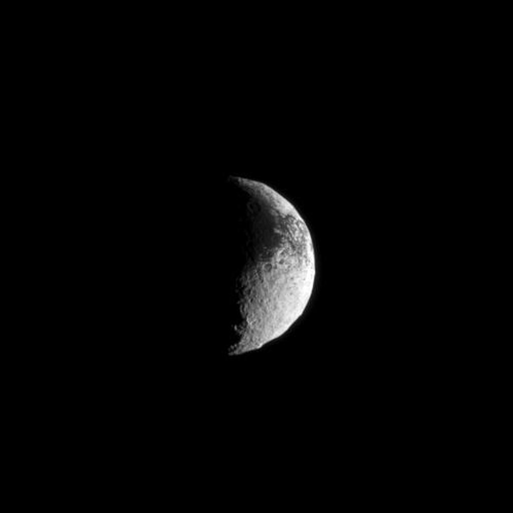Light and dark terrain covers the surface of Saturn's moon Iapetus in this view from NASA's Cassini spacecraft.