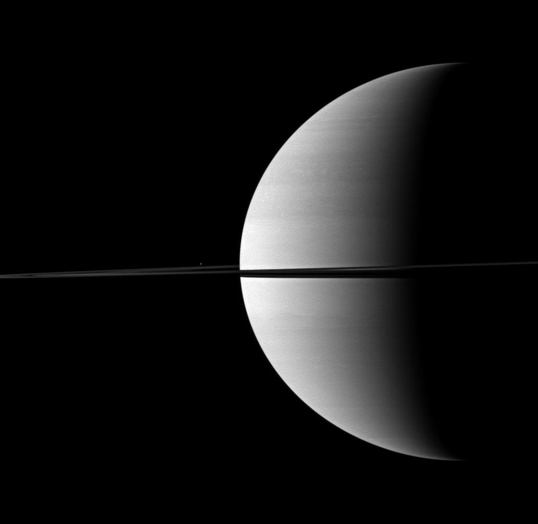 Nearly invisible upon first glance, Saturn's moon Enceladus is a small bright dot beyond the planet's rings in this image taken by NASA's Cassini spacecraft.