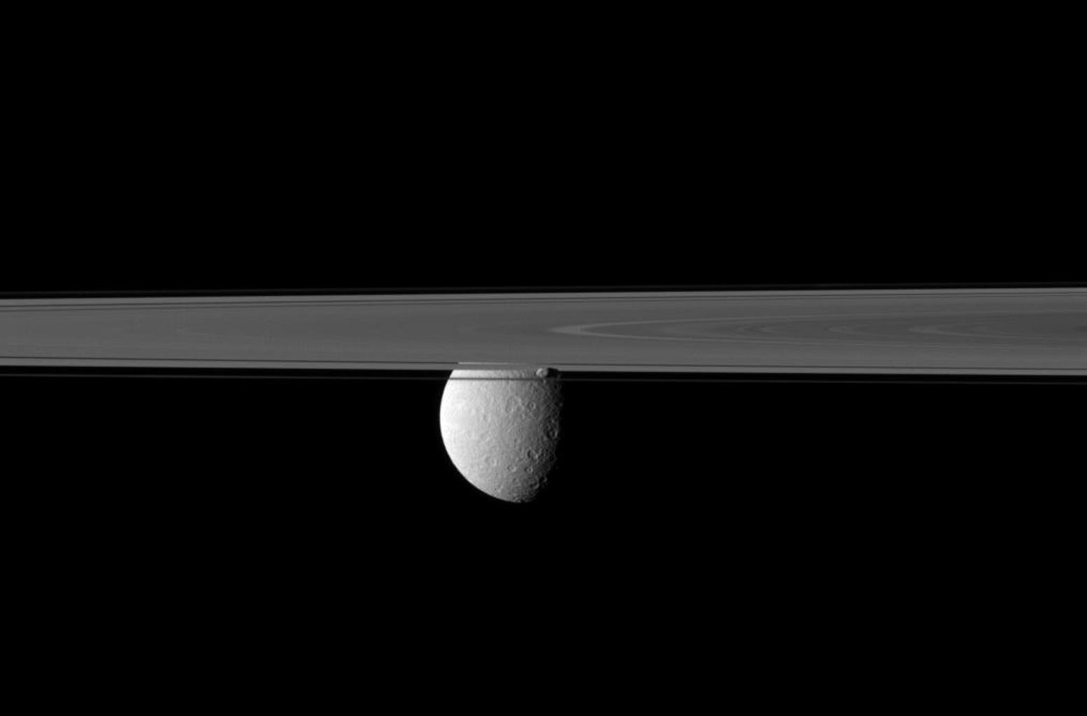 Saturn's rings and small moon Prometheus obscure NASA's Cassini spacecraft's view of the planet's second largest moon, Rhea. Prometheus can be seen just below the center of the image, in front of Rhea.