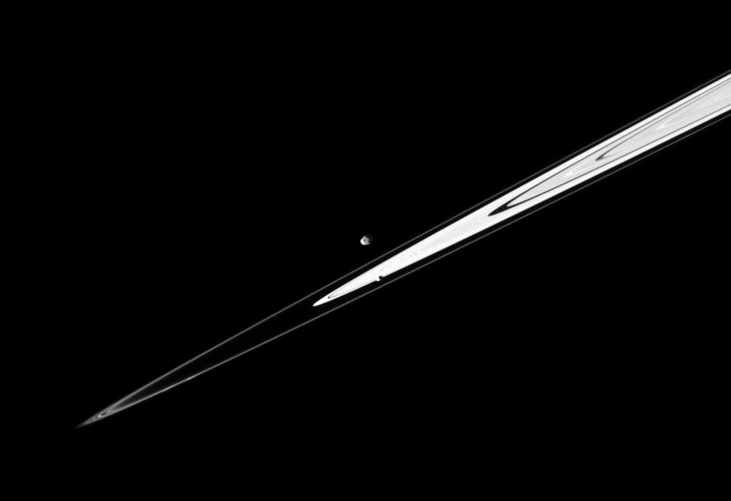 A pair of Saturn's small satellites, Janus and Pandora, accompany the planet's rings in this image from NASA's Cassini spacecraft presenting the view in dramatic diagonal fashion.