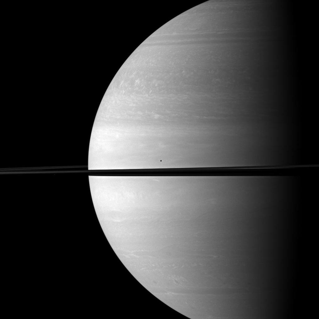 The moons Mimas and Janus seem insignificant in front of the immensity of Saturn in this NASA Cassini spacecraft image. Mimas is visible above the rings near the center; Janus is barely detectable as a tiny speck of light below the rings on the left.