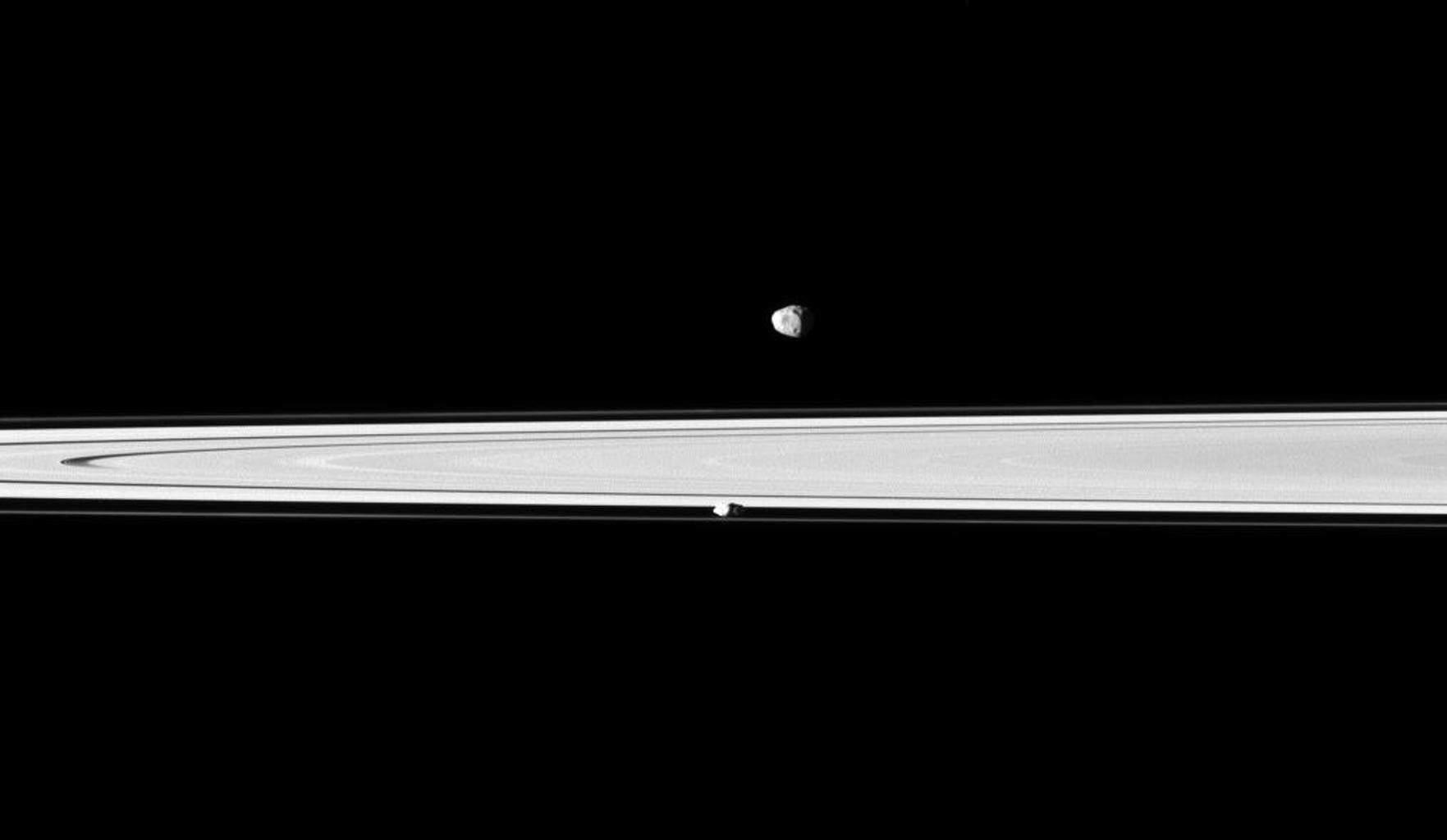 A pair of Saturn's small, icy satellites accompany the planet's rings in snapshot from NASA's Cassini spacecraft. The rings are between Janus and Prometheus.