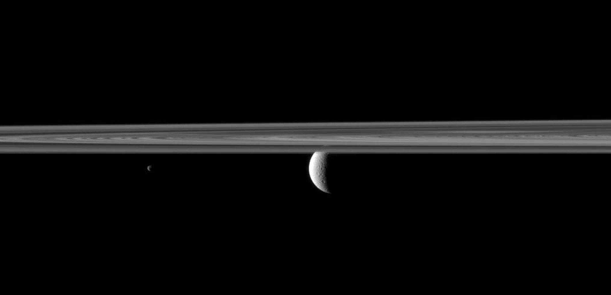 NASA's Cassini spacecraft looks past Saturn's rings and small moon Janus to spy the planet's second largest moon, Rhea where lit terrain is seen.