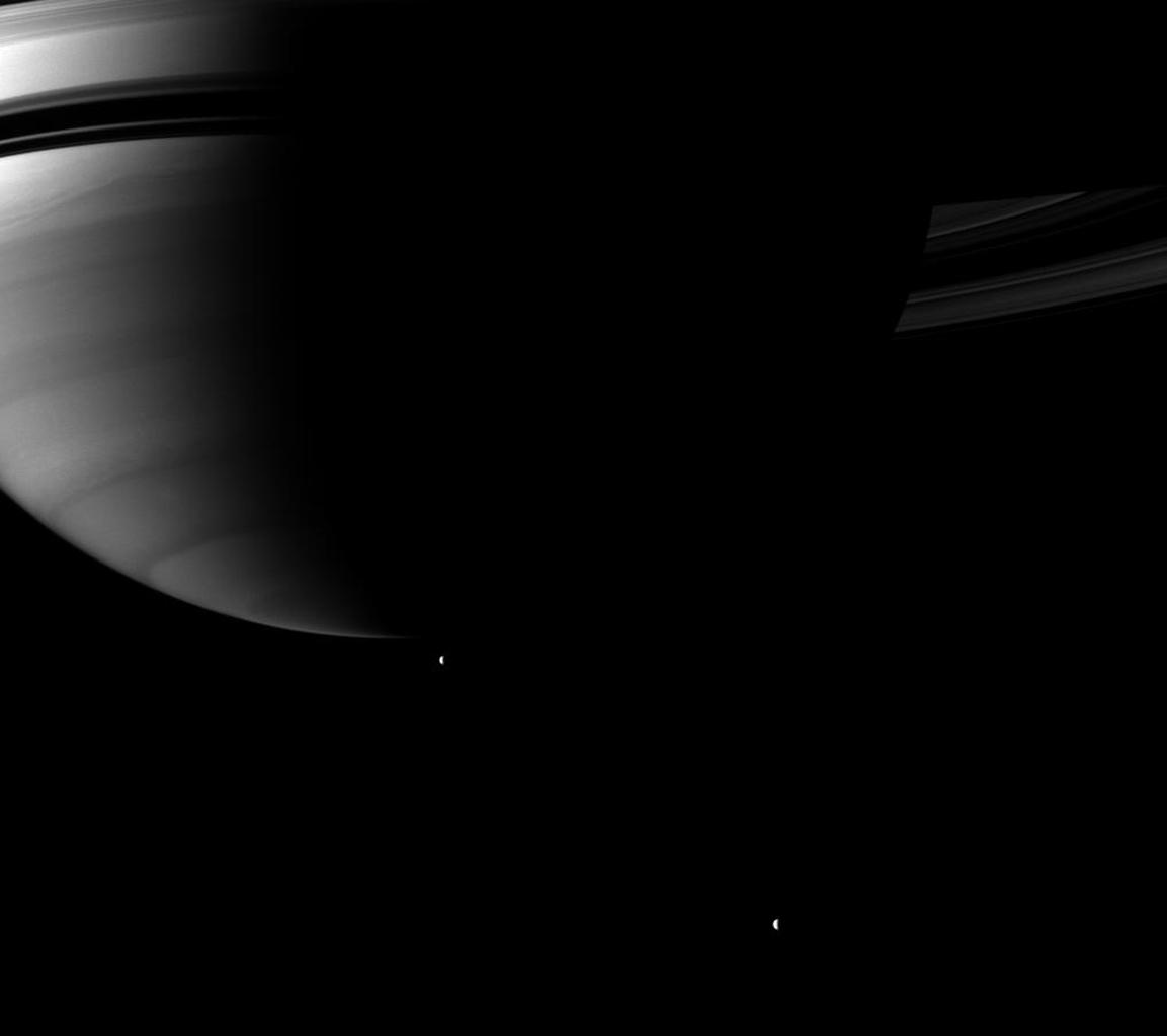 Looking up toward Saturn's southern hemisphere, NASA's Cassini spacecraft pictures a pair of the planet's moons orbiting in the distance. Tethys and Rhea orbit in the plane of the planet's rings, but appear to be below the planet in this view.