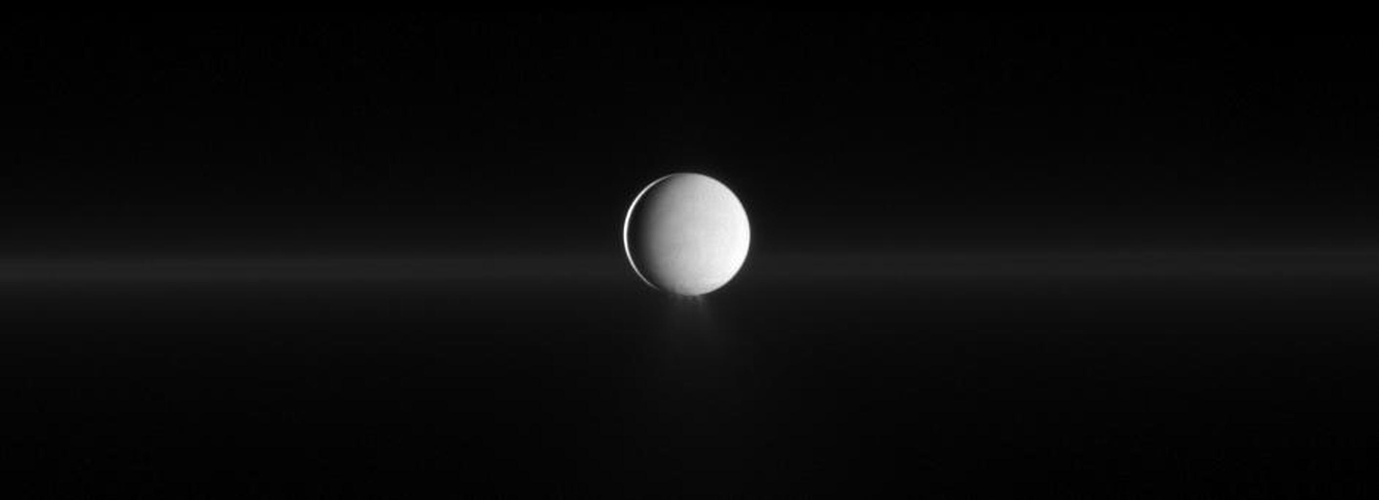 As Enceladus spews water ice from its south polar region, NASA's Cassini also shows Saturn's faint G ring before the moon.
