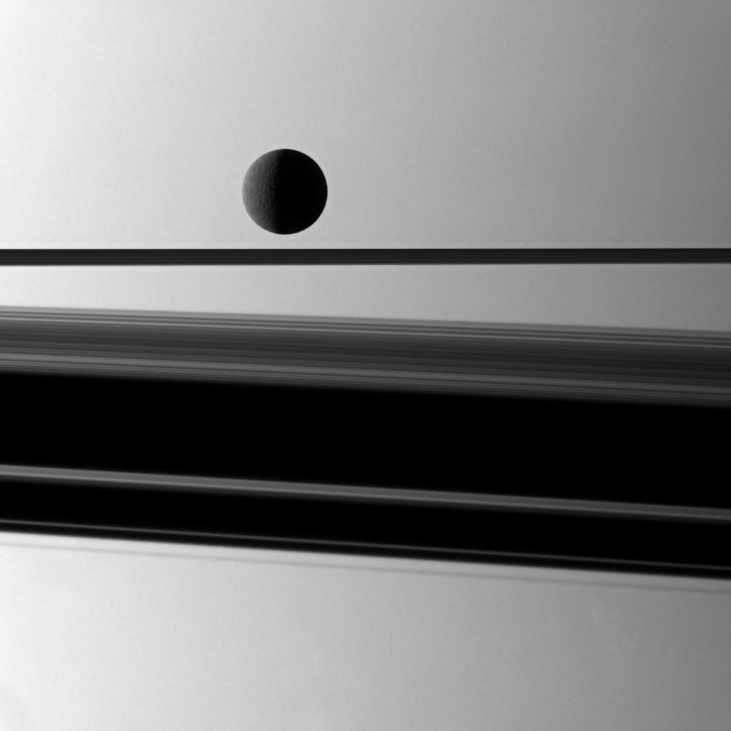 Saturn's moon Rhea is gently lit in front of a background of the planet with a wide shadow cast by the rings which are seen nearly edge-on in this image captured by NASA's Cassini spacecraft.