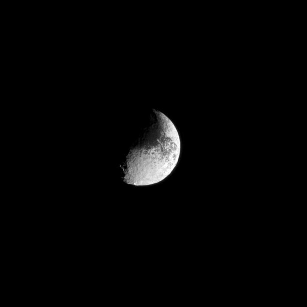 With its light and dark surface, Iapetus appears almost like a yin and yang symbol or a comma punctuation mark in this Cassini spacecraft image.