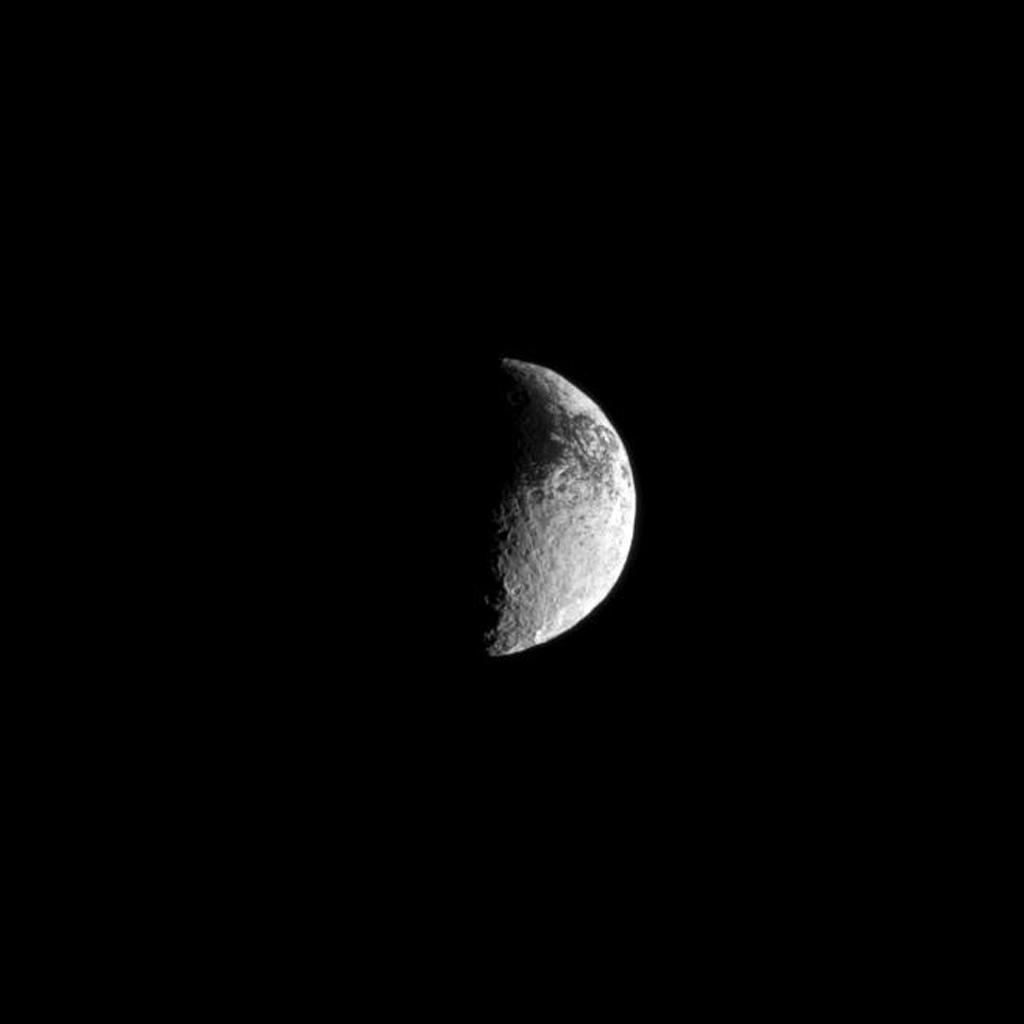 Some of Iapetus' dark surface interrupts the moon's lighter terrain in this view from NASA's Cassini spacecraft.