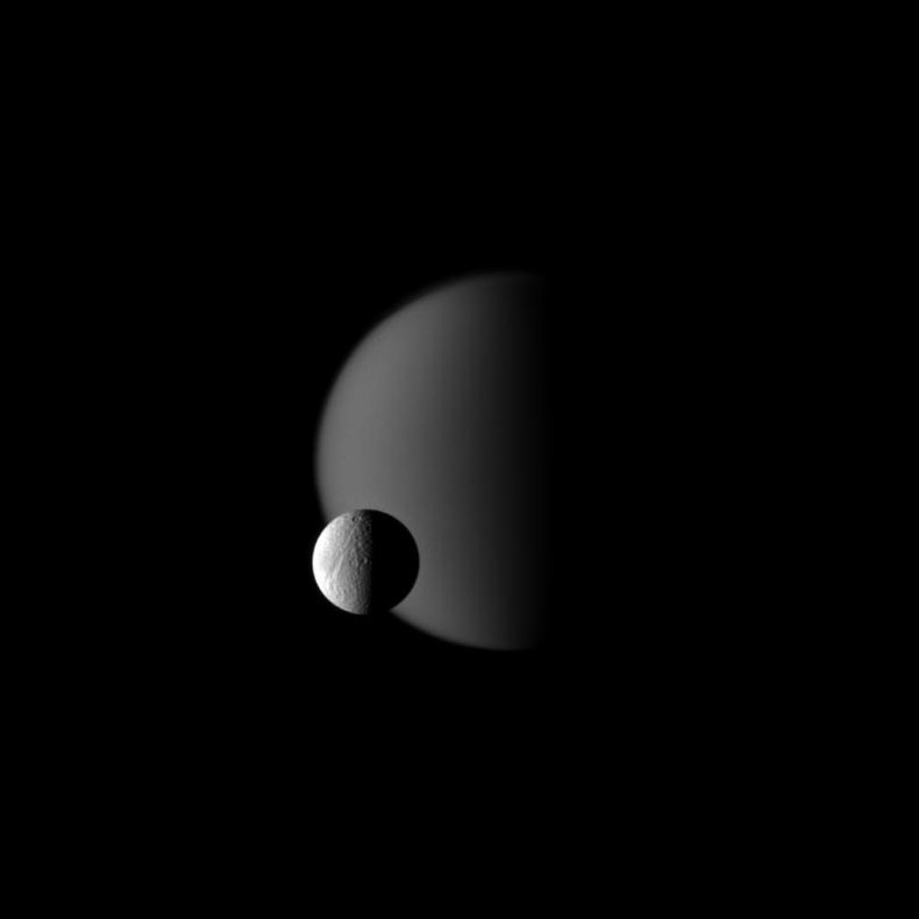 Terrain on Saturn's moon Tethys, defined with craters, is shown in front of the hazy atmosphere of the larger moon Titan in this image from NASA's Cassini spacecraft. This view looks toward the Saturn-facing sides of Titan and Tethys.
