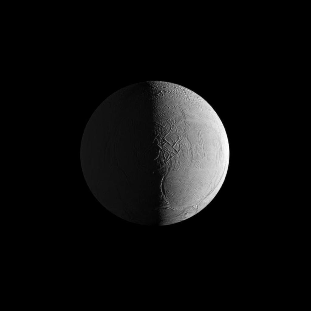 Two sources of light reveal the dramatic surface of Saturn's moon Enceladus in this NASA Cassini image in which geologic features give the appearance of the leathery skin of an elephant.