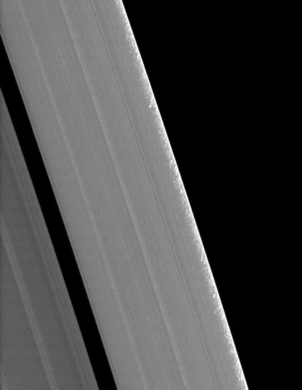 Clumps of ring material are revealed along the edge of Saturn's A ring in this image taken during the planet's August 2009 equinox. The granular appearance of the outer edge of the A ring is likely created by gravitational clumping of particles there.