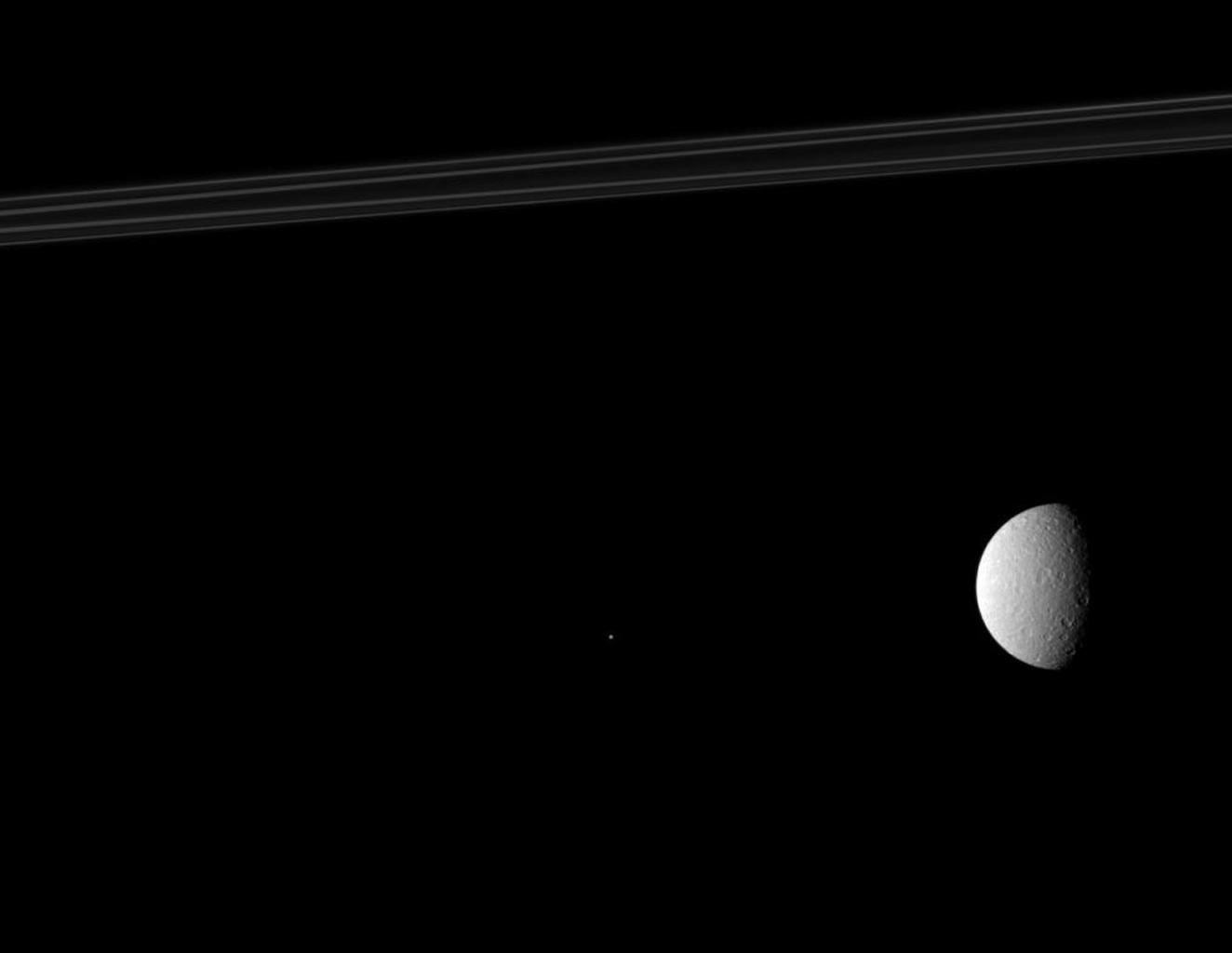 NASA's Cassini spacecraft composition features Saturn's rings (top of image), its second largest moon, Rhea (on right of image), and one of the planet's tiny moons, Telesto (near the middle of image) appears as a bright speck.