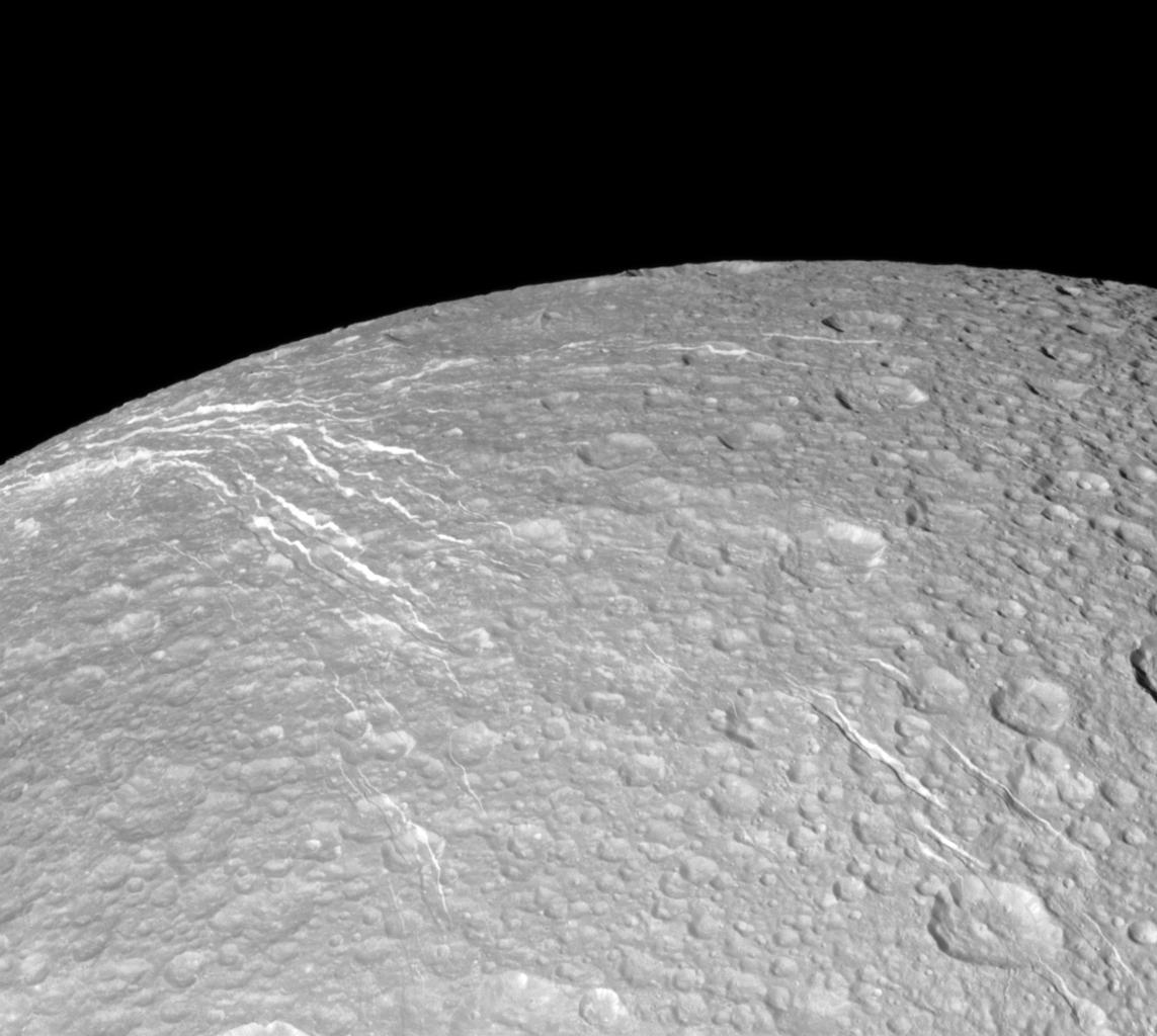 "NASA's Cassini spacecraft looks across the surface of Saturn's moon Dione and details the ""wispy"" terrain first chronicled by Voyager. This fractured terrain covers the trailing hemisphere of Dione."