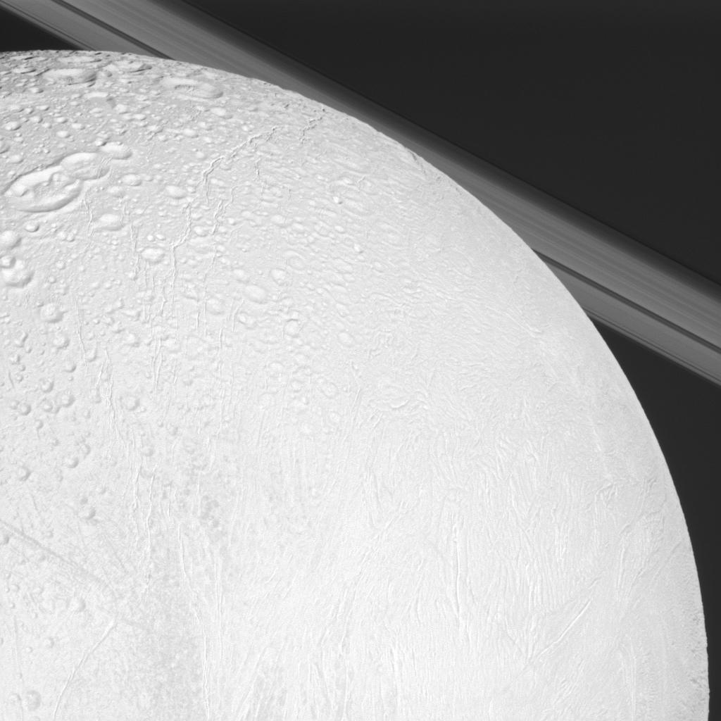 NASA's Cassini spacecraft looks over cratered and tectonically deformed terrain on Saturn's moon Enceladus as the camera also catches a glimpse of the planet's rings in the background.