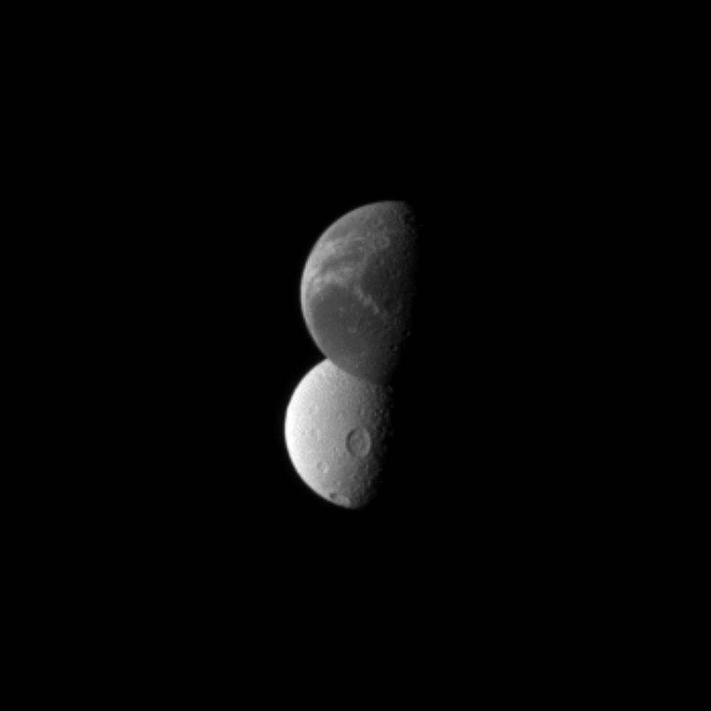 Saturn's 'wispy' moon Dione lies in front of the cratered surface of the moon Tethys, as seen by NASA's Cassini spacecraft. Dione is closest to the spacecraft here.