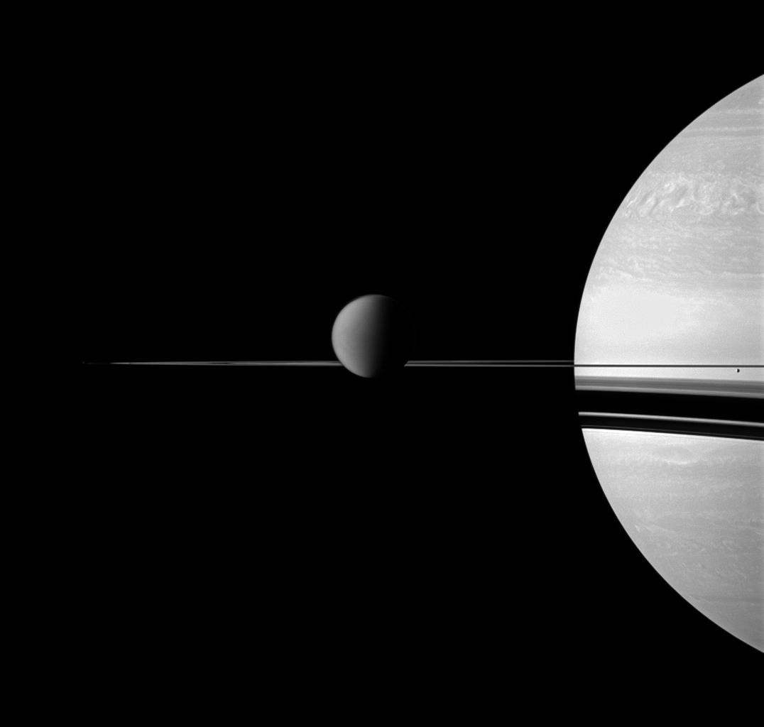 NASA's Cassini spacecraft views Saturn with a selection of its moons in varying sizes. Also seen here are Titan (center), Enceladus (far right), Pandora, barely detectable as a speck on the far left, has been brightened by a factor of two.