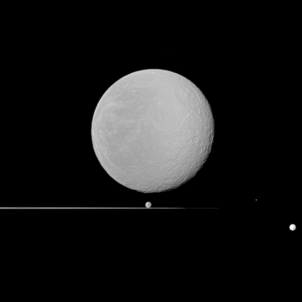 Five moons, dominated by Rhea in the foreground, share NASA's Cassini spacecraft view with Saturn's rings seen nearly edge-on. Also seen here are Dione, Epimetheus, Prometheus, and Tethys.