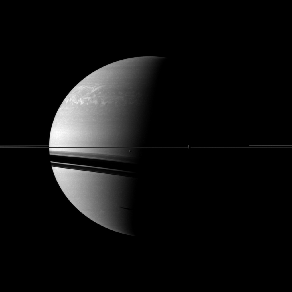 Two moons, Rhea and Dione, join the planet and its rings in this view from NASA's Cassini spacecraft. Rhea and Dione are respectively the second and fourth largest moons of Saturn, but they are tiny compared to the planet.