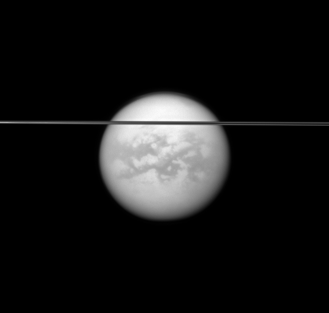 Saturn's rings cut across this view of the planet's largest moon, Titan. Dark albedo features on Titan (5,150 kilometers, or 3,200 miles across) and the moon's north polar hood are visible in this image captured by NASA's Cassini spacecraft.