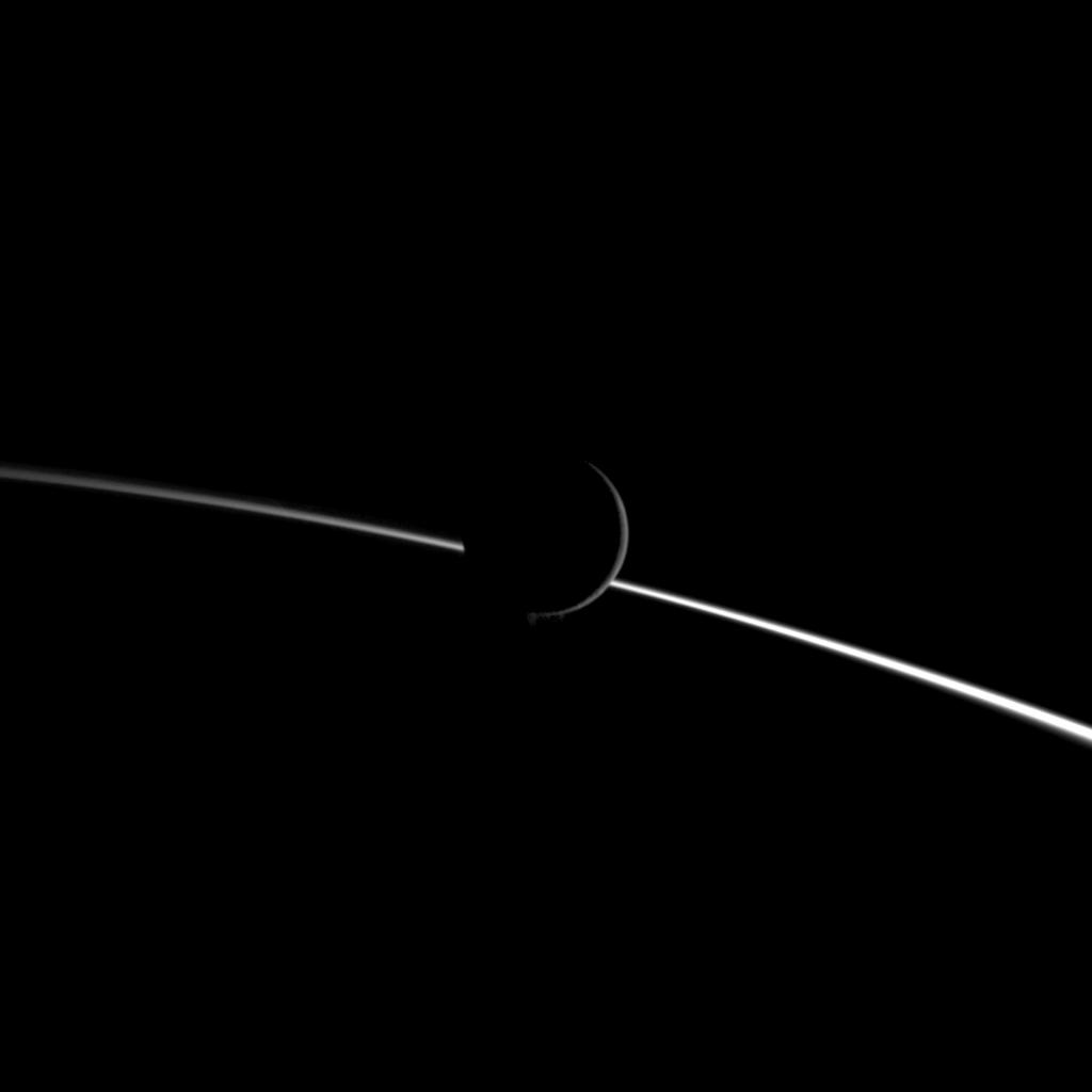 Jets of water ice particles spew from Saturn's moon Enceladus in this image obtained by NASA's Cassini spacecraft on Aug. 13, 2010. A crescent of the moon appears dimly illuminated in front of the bright limb of Saturn.