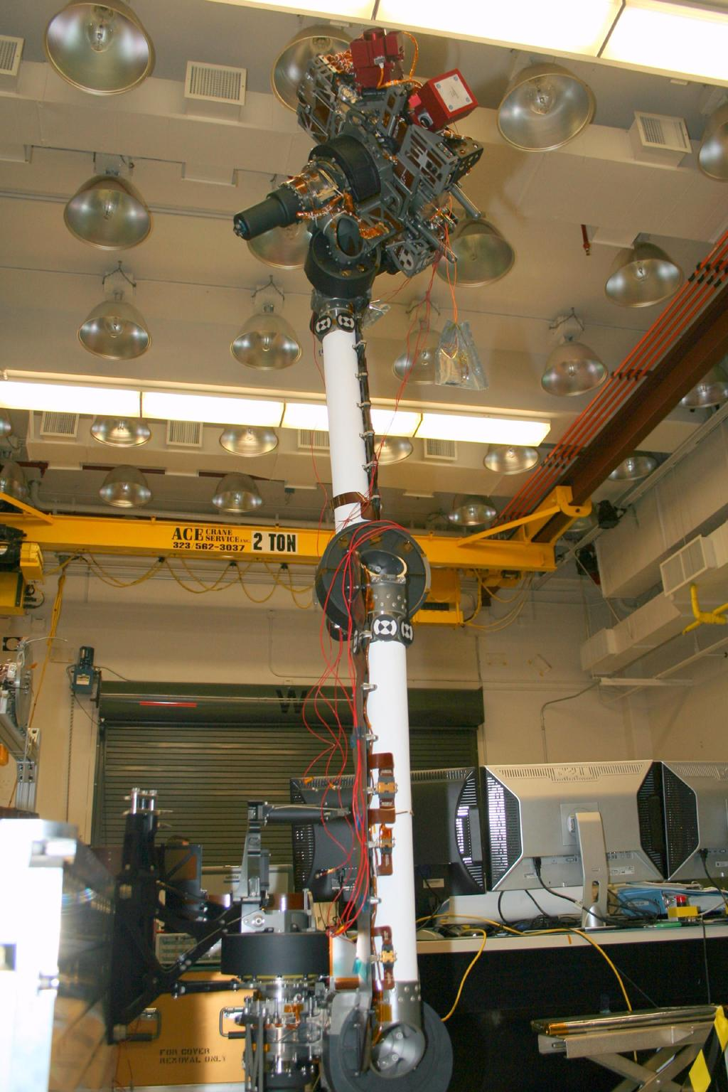 In the middle of this image taken at the Jet Propulsion Laboratory, the long robotic arm of NASA's Mars Science Laboratory rises straight up toward the ceiling of the lab where it is being tested.