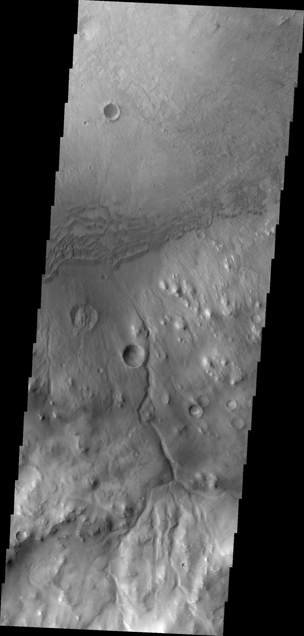 This image, taken by NASA's 2001 Mars Odyssey spacecraft, shows a portion of the rim and floor of Gale Crater. The crater rim is dissected by a channel, and dunes are located on the floor at the rim margin.