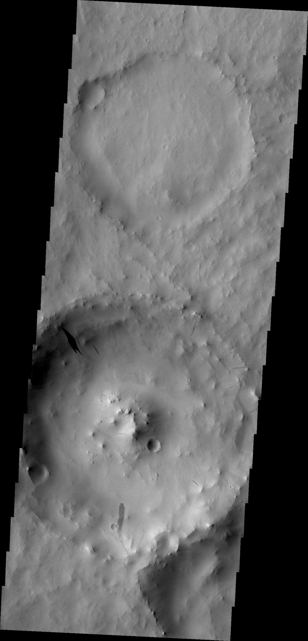 Dark slope streaks, like the ones in this unnamed crater in Terra Sabaea, are believed to be formed when surface dust is displaced and the darker rock below is exposed. Rocks falling due to gravity likely formed these streaks.