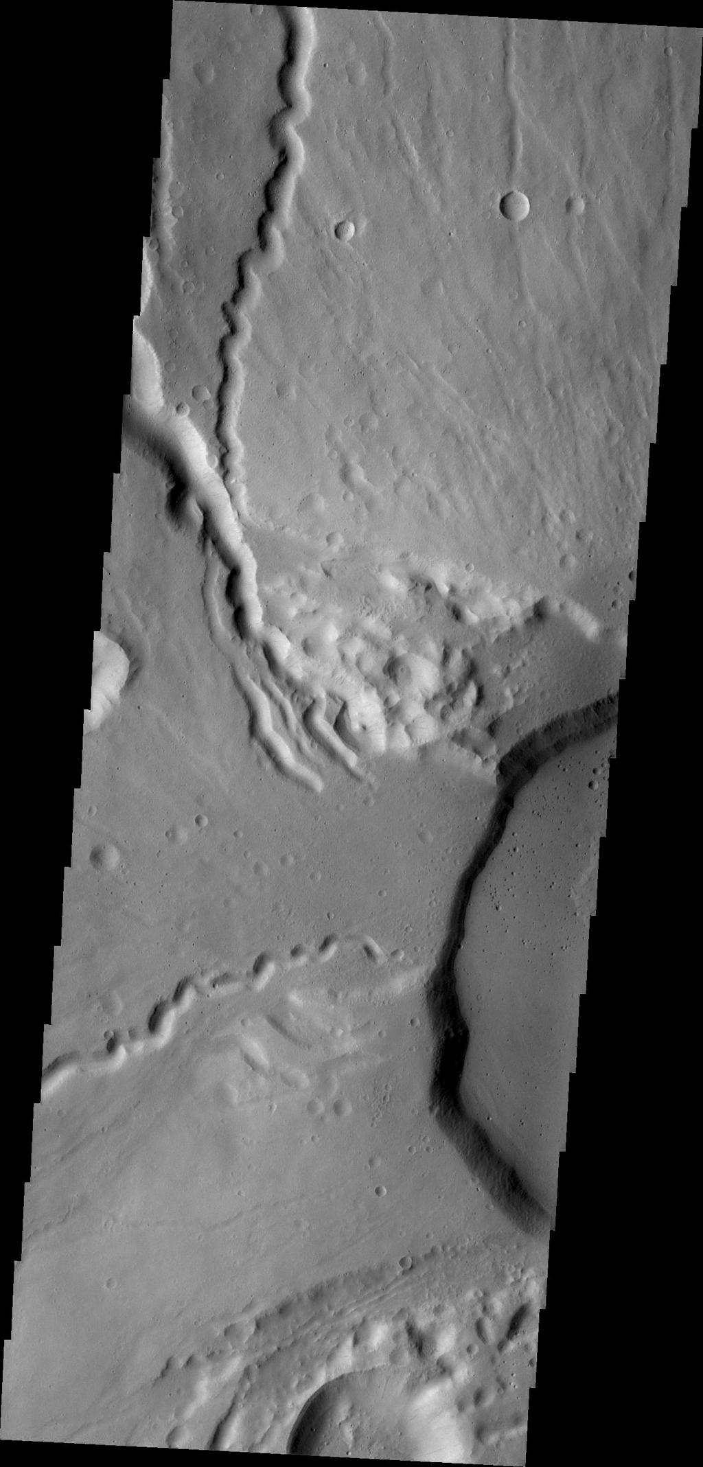 This NASA 2001 Mars Odyssey spacecraft image shows the western edge of the summit caldera of Ceranus Tholus, one of the smaller volcanic constructs of the Tharsis region. Several channels dissect the western flank of the volcano.