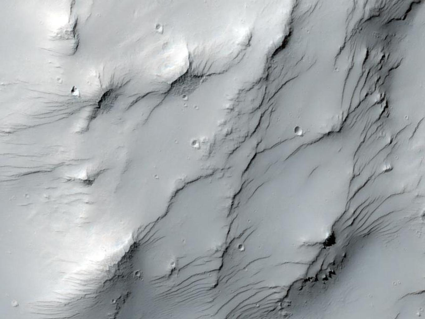 This image captured by NASA's Mars Reconnaissance Orbiter covers some high-standing topography just outside the rim of an impact crater about 30 kilometers (19 miles) in diameter near a Martian hill named Zephyria Tholus.