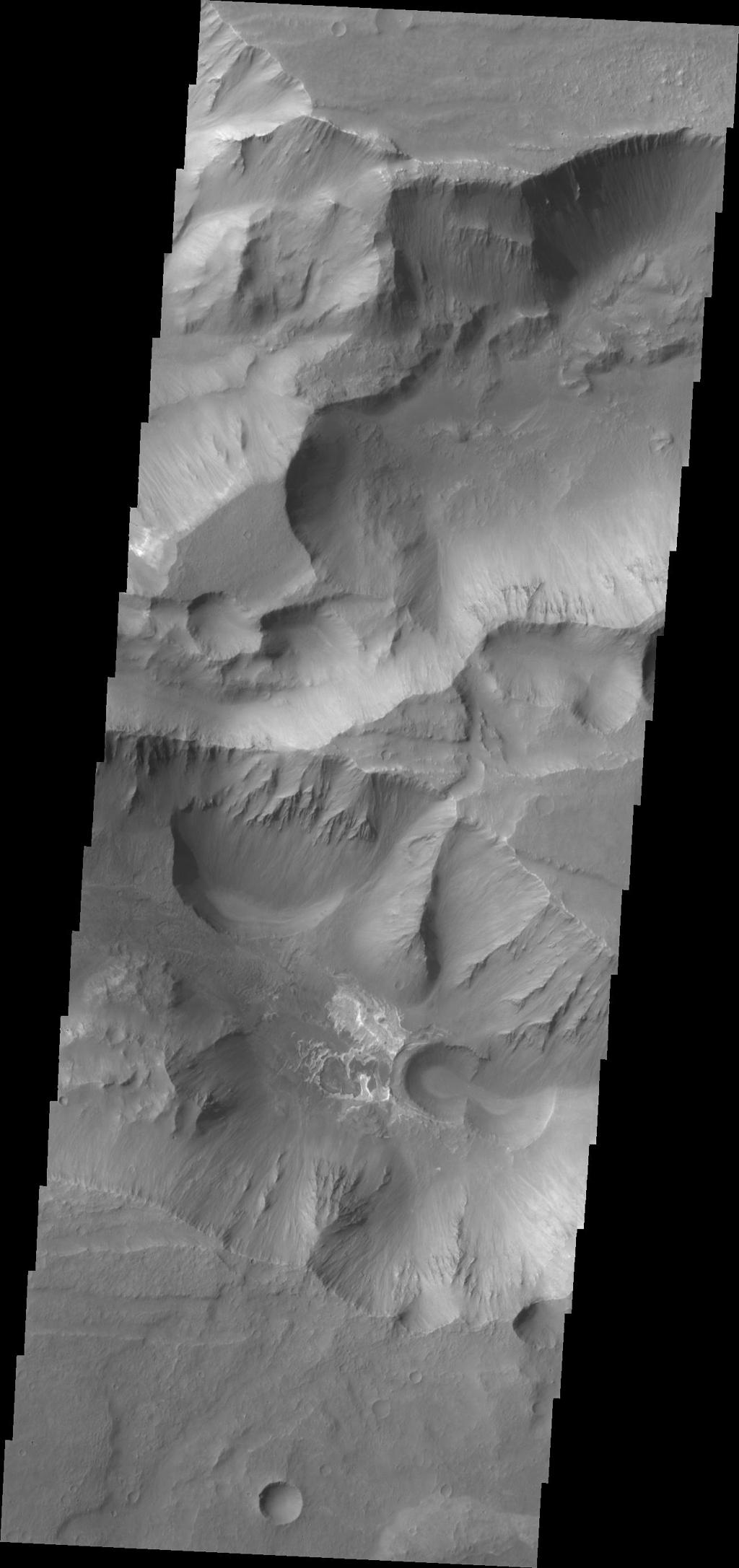 This image from NASA's 2001 Mars Odyssey spacecraft shows a small portion of the floor of Coprates Catena, just south of the Valles Marineris canyon system. The lighter toned materials in the center of the image are layered deposits.