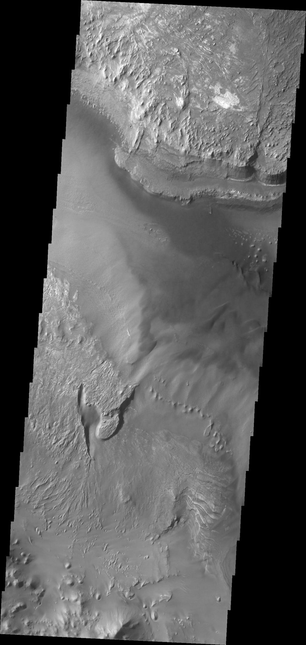 Melas Chasma is the central portion of Valles Marineris. This image taken by NASA's 2001 Mars Odyssey shows a small portion of the floor of Melas Chasma, including layered deposits and wind eroded and deposited materials.