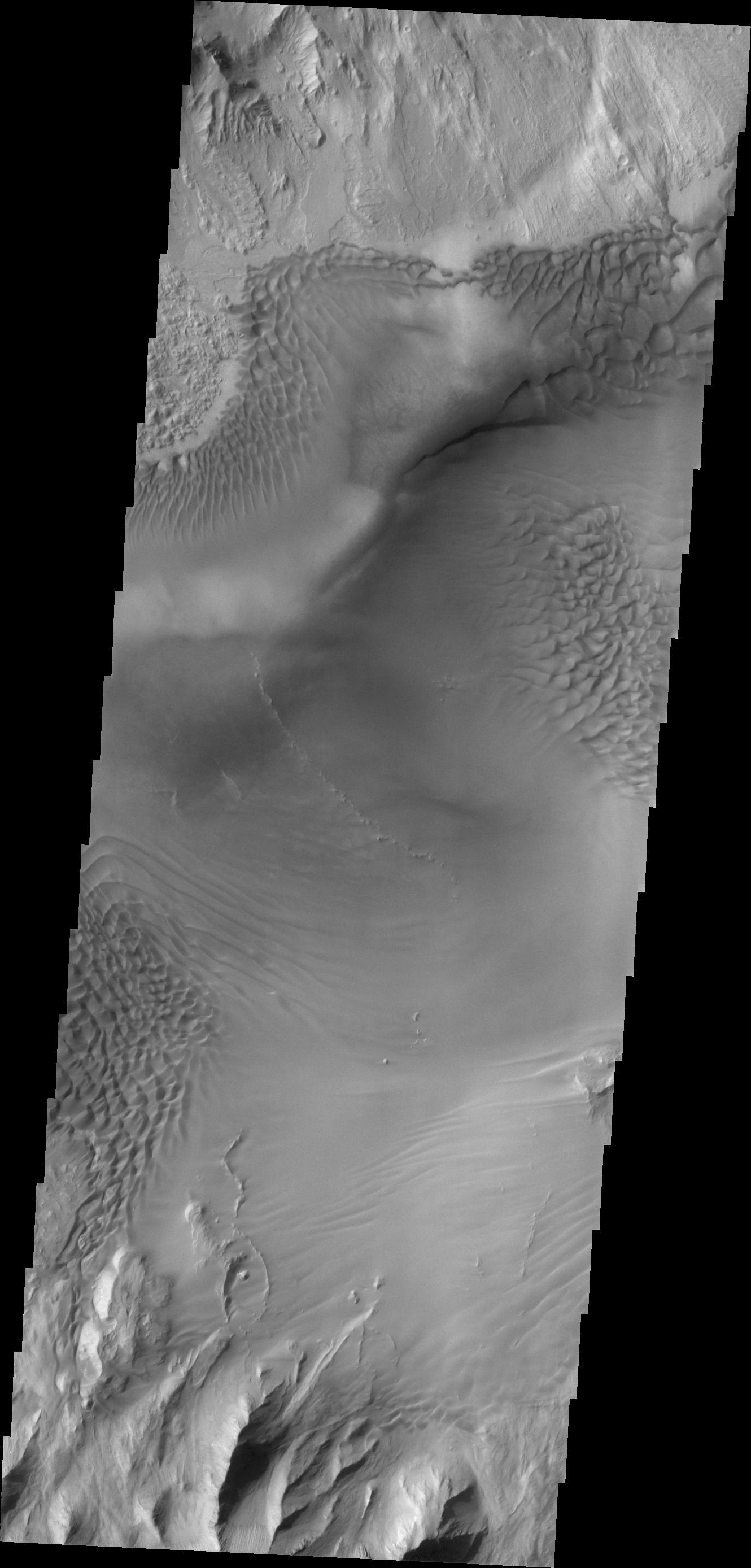 Baetis Chasma is a chasmata near but not directly connected to Valles Marineris. Dunes are prevalent on the floor of this portion of Juventae Chasma in this image taken by NASA's 2001 Mars Odyssey.