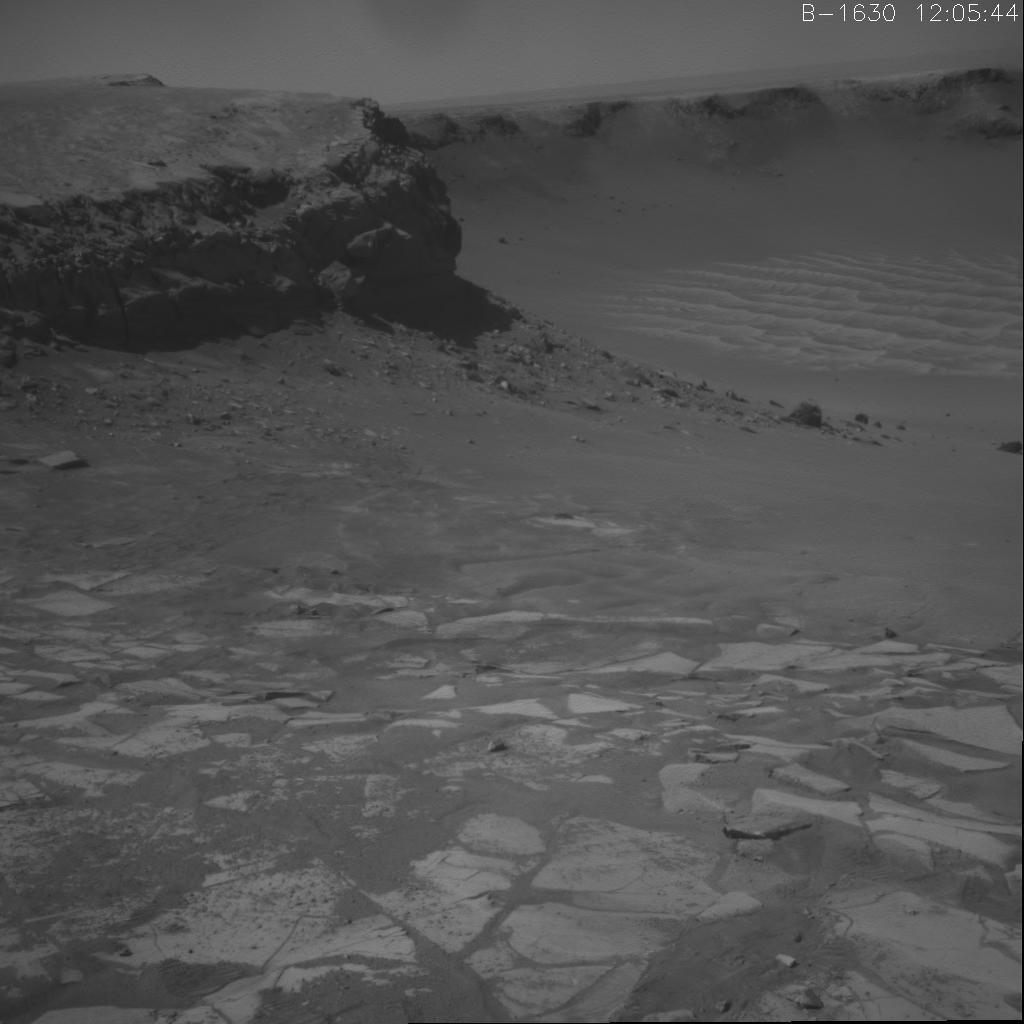 "This image shows NASA's Opportunity's climb out of Victoria crater. It is the first frame of a movie that spans three days when the rover exited the crater at the alcove called ""Duck Bay"" leaving two sets of wheel tracks."
