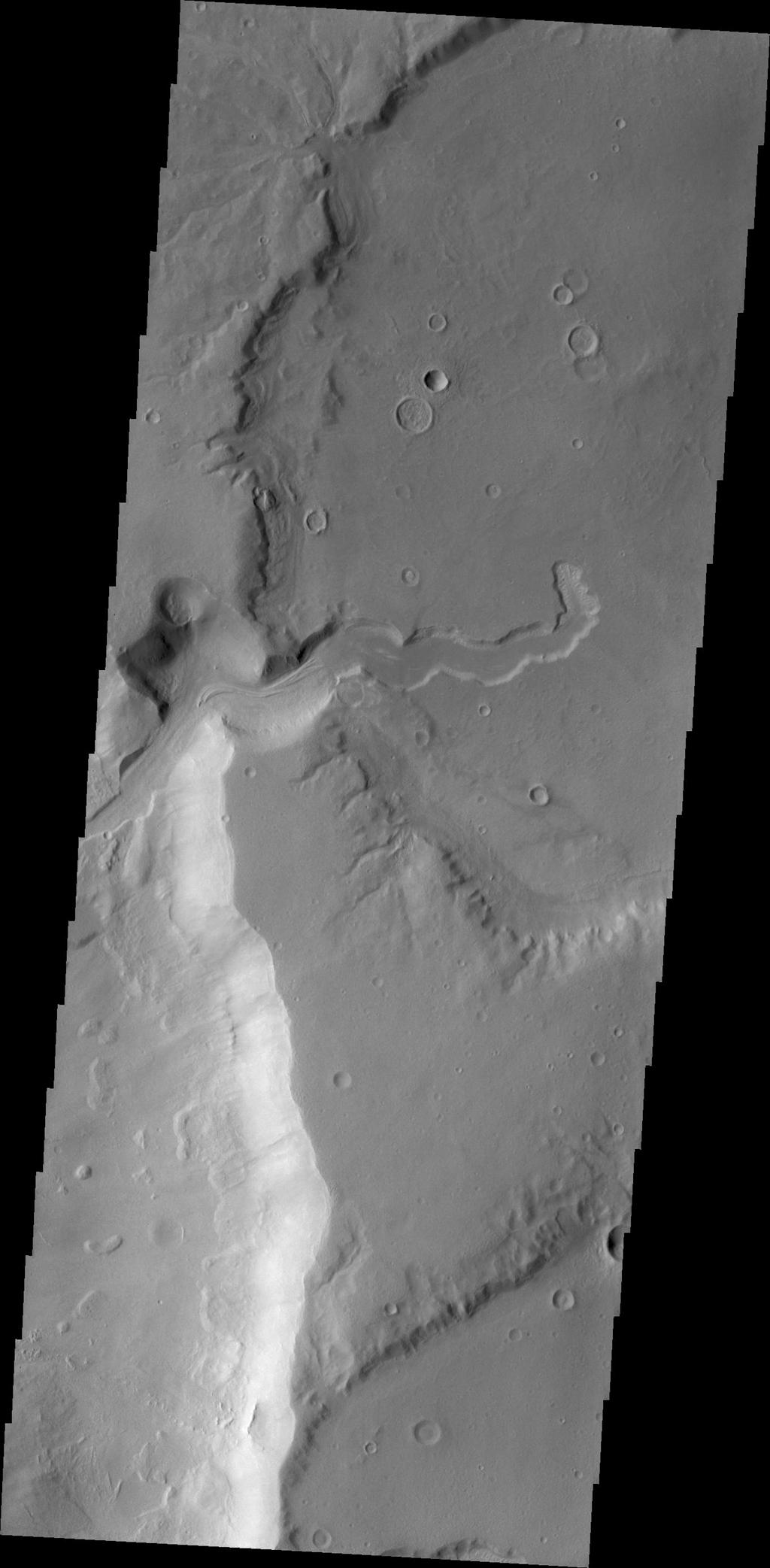 This image captured by NASA's 2001 Mars Odyssey shows a small channel emptying into a deeper crater to the west.