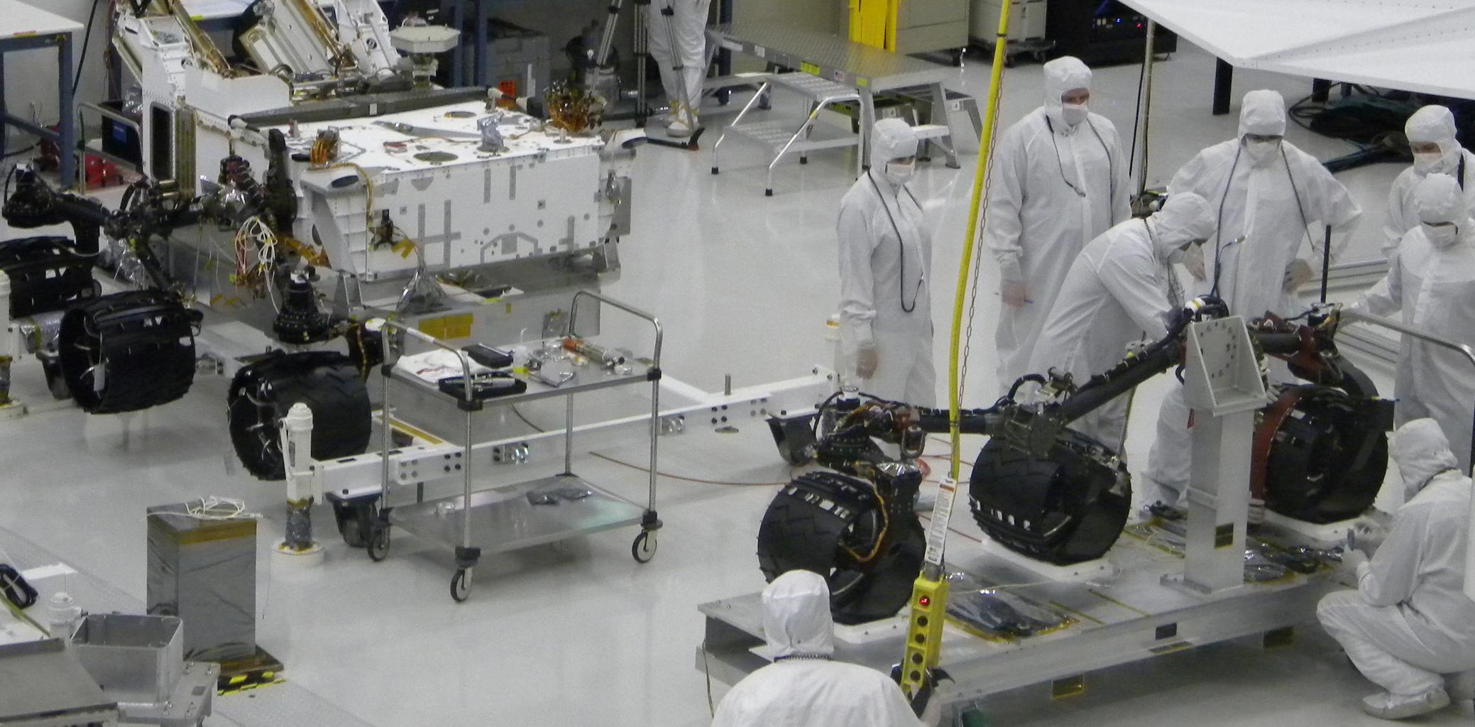 With the wheels and suspension system already installed onto one side of NASA's Mars rover Curiosity the previous day, spacecraft engineers and technicians prepare the other side's mobility subsystem for installation on June 29, 2010.