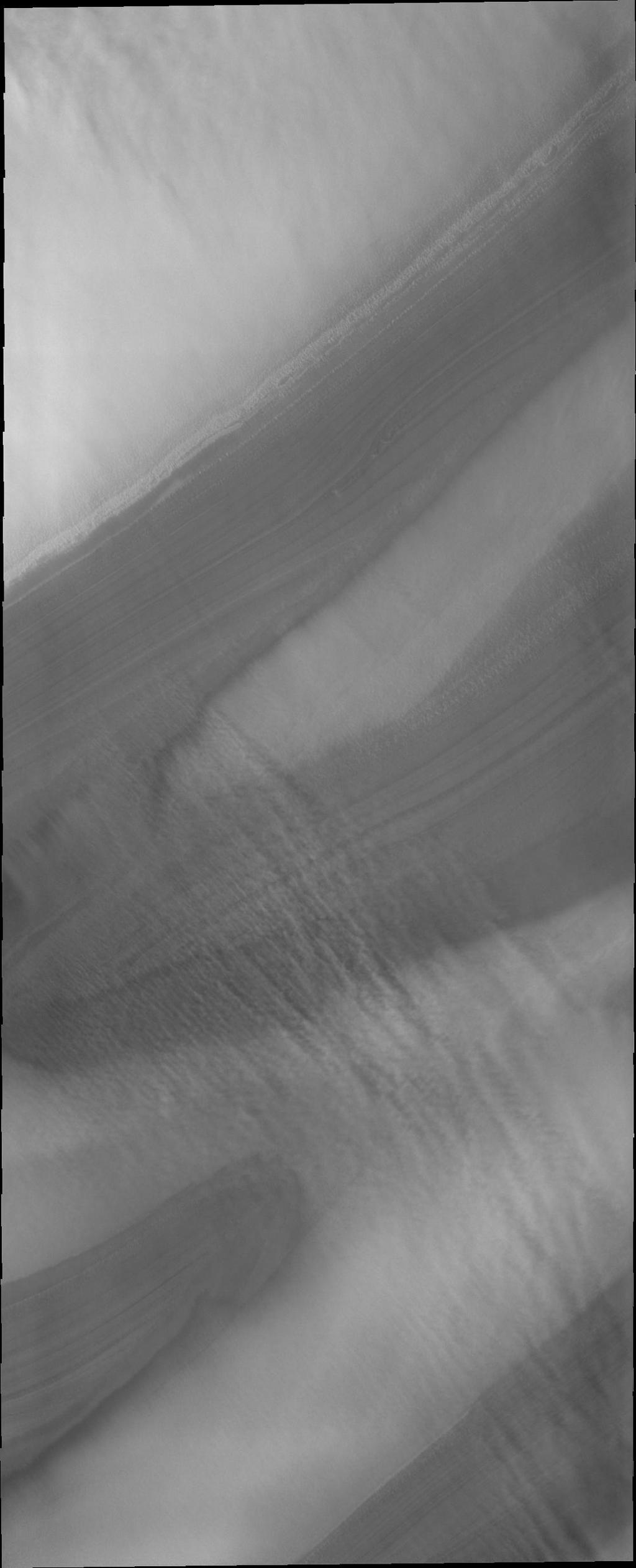 North polar troughs are the typical location to see evidence of strong polar surface winds. This image captured by NASA's 2001 Mars Odyssey shows 'streamers' of clouds created by catabatic winds.