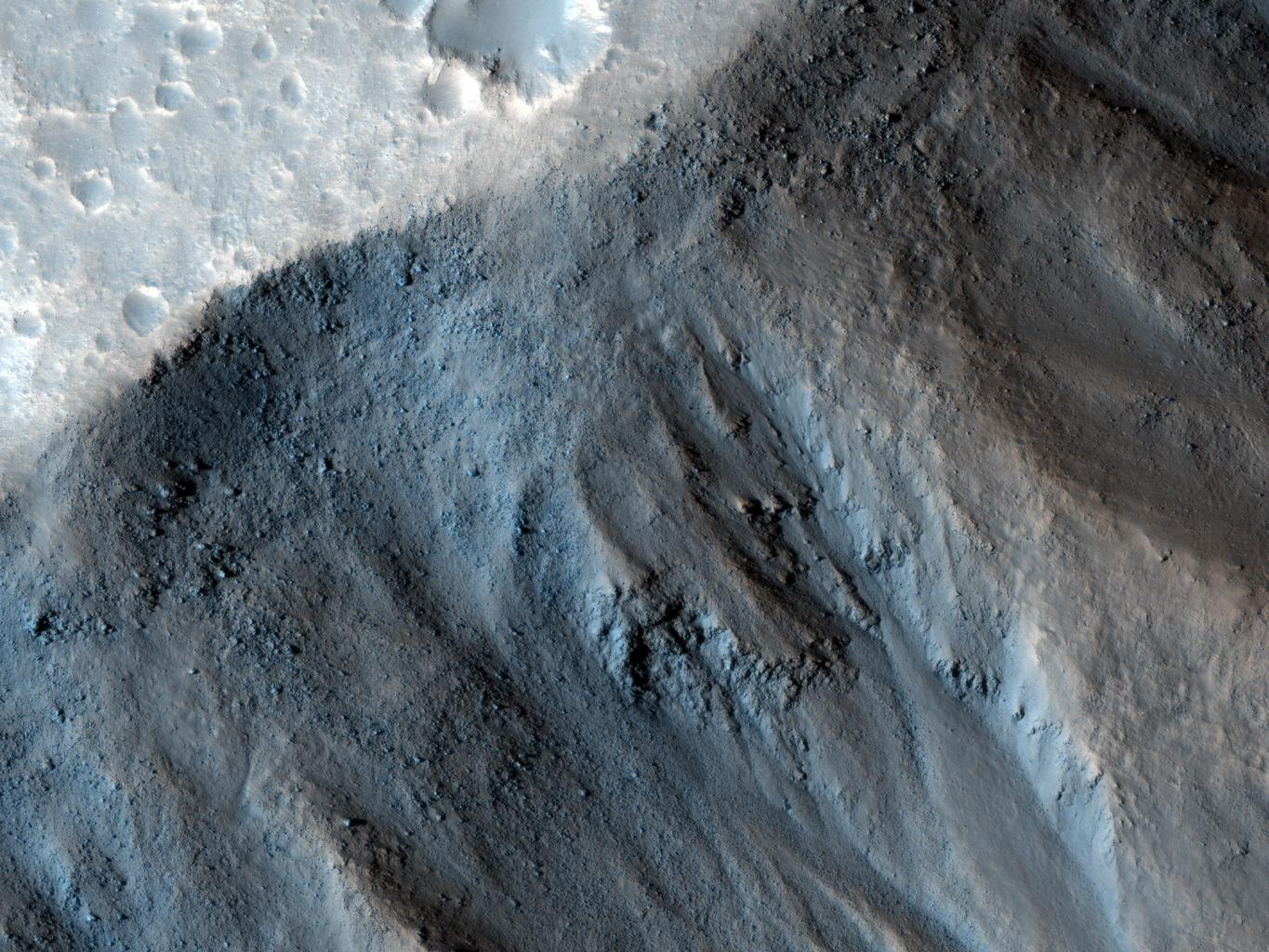 This observation from NASA's Mars Reconnaissance Orbiter shows the very steep side of a plateau, part of the northern limit of the Kasei Valles system, which is one of the largest outflow channel systems on Mars.