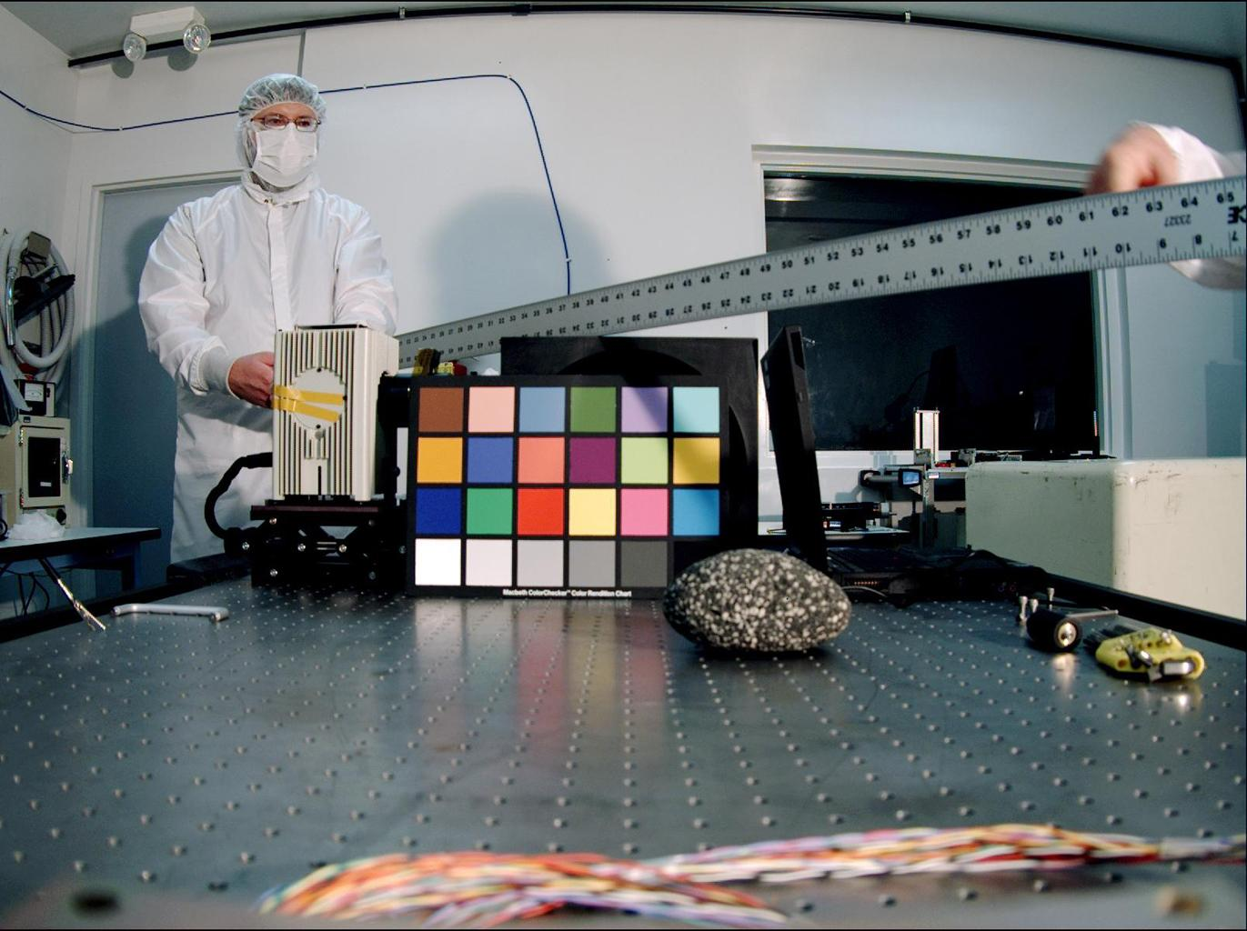 Ken Edgett, deputy principal investigator for NASA's Mars Descent Imager, holds a ruler used as a depth-of-field test target. The instrument took this image inside the Malin Space Science Systems clean room in San Diego, CA, during calibration testing.