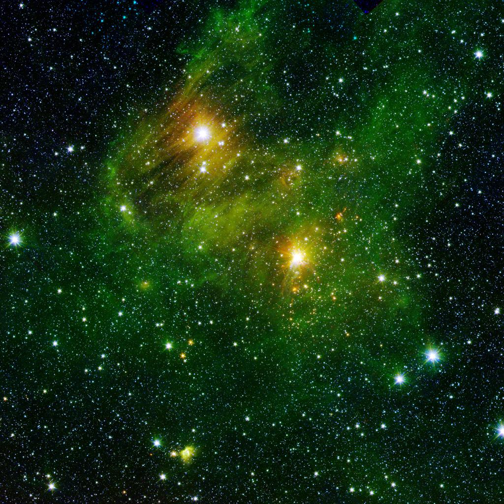 "Two extremely bright stars illuminate a greenish mist in this image from the new ""GLIMPSE360"" survey from NASA's Spitzer Space Telescope. The fog is comprised of hydrogen and carbon compounds called polycyclic aromatic hydrocarbons."