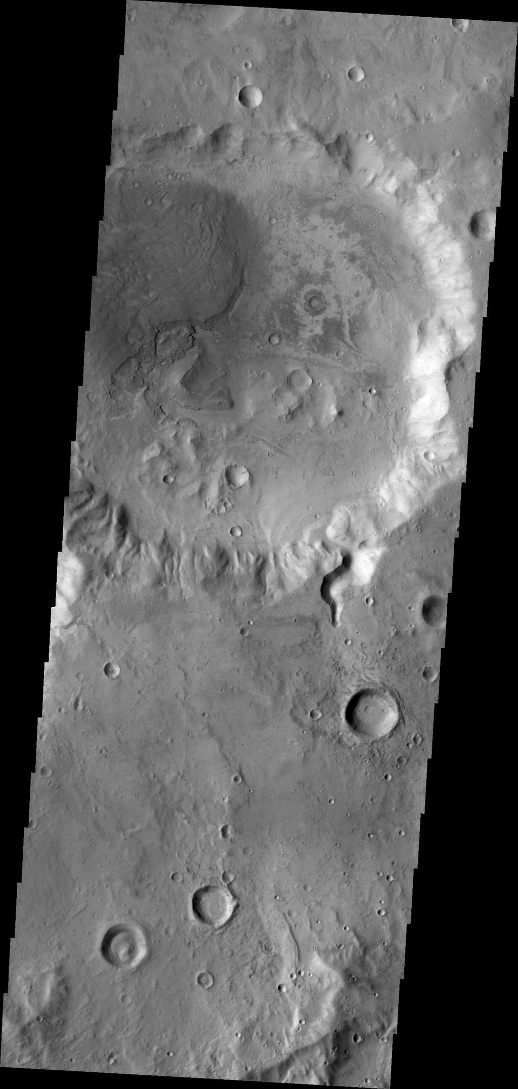 A small channel enters this unnamed crater in Arabia Terra. There appears to be a small fan or delta formed where the channel meets the crater floor. This image was captured by NASA's Mars Odyssey on June 15, 2010.
