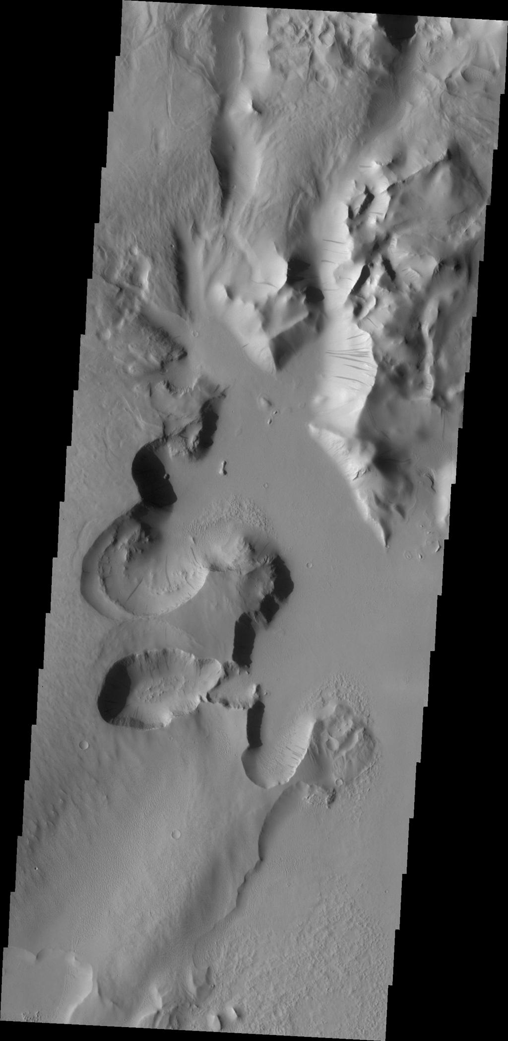 Lycus Sulci is an extremely complex region surrounding the western and northern flanks of Olympus Mons. With a multitude of fault formed cliff faces, dark slope streaks are a common occurrence. This image was captured by NASA's Mars Odyssey.