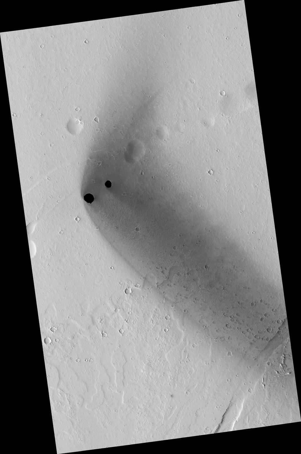 Two dark, rimless pits are located to the northwest of Ascraeus Mons in the Tharsis volcanic region of Mars in this image from NASA's Mars Reconnaissance Orbiter. They are situated in the midst of a wispy, dark, boomerang-shaped deposit.